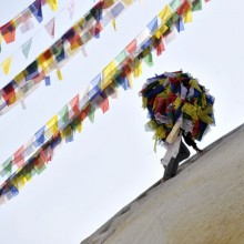 Carrying prayer flags up a stupa in Boudhanath, Nepal