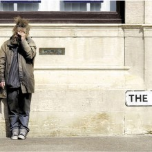 Homeless man shields his eyes from the sun, London